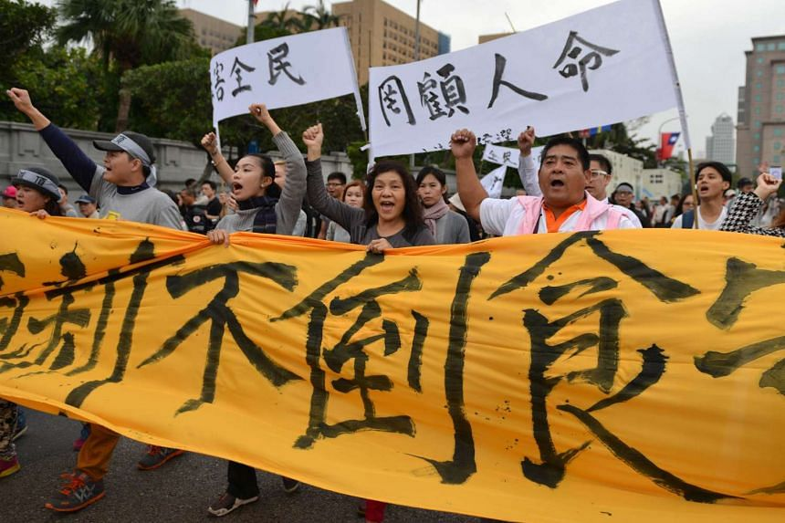 Taiwanese protesters holding up banners and placards during a demonstration in Taipei.