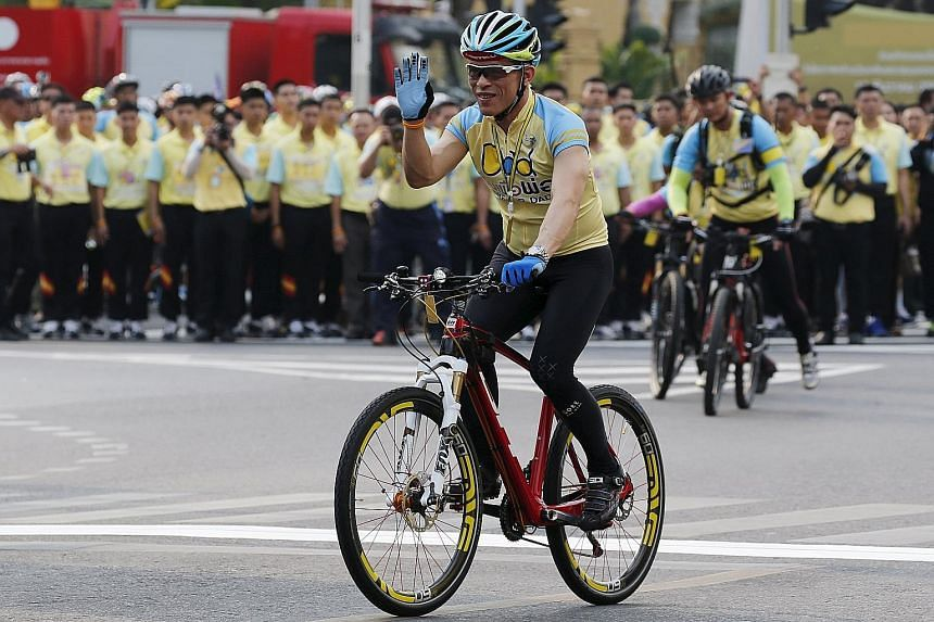 """Crown Prince Maha Vajiralongkorn waving to crowds at the """"Bike for Dad"""" event in Bangkok yesterday. He led about 100,000 cyclists on a 29km course in Bangkok to celebrate King Bhumibol's 88th birthday, which fell on Dec 5."""