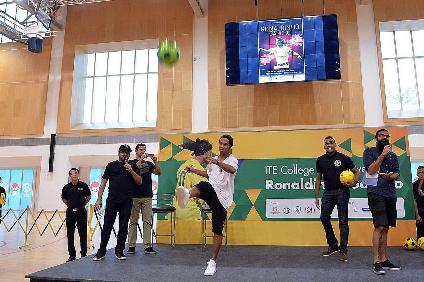 Ronaldinho kicking an autographed football into the capacity crowd at ITE College Central's multi-purpose hall during his 15-minute appearance yesterday.