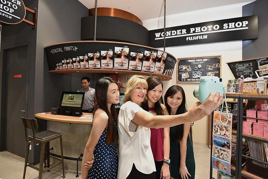 Harvey Norman chief executive Katie Page (second from left) posing for a wefie on Thursday with staff (from left) Gina Chan, Samantha Wong and Fiona Low at Singapore's first Fujifilm Wonder Photo Shop in the new Harvey Norman store in Millenia Walk.