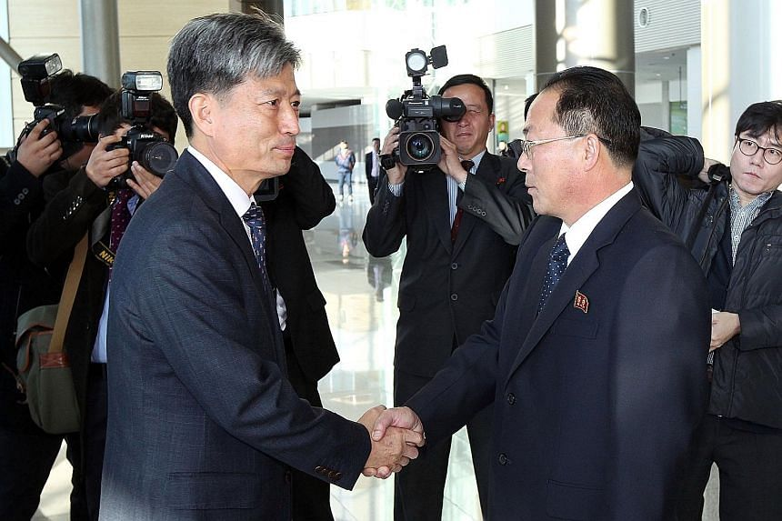 South Korea's Vice-Unification Minister Hwang Boo Gi (left) shaking hands with his counterpart from the North, Mr Jon Jong Su, before their meeting in Kaesong yesterday.