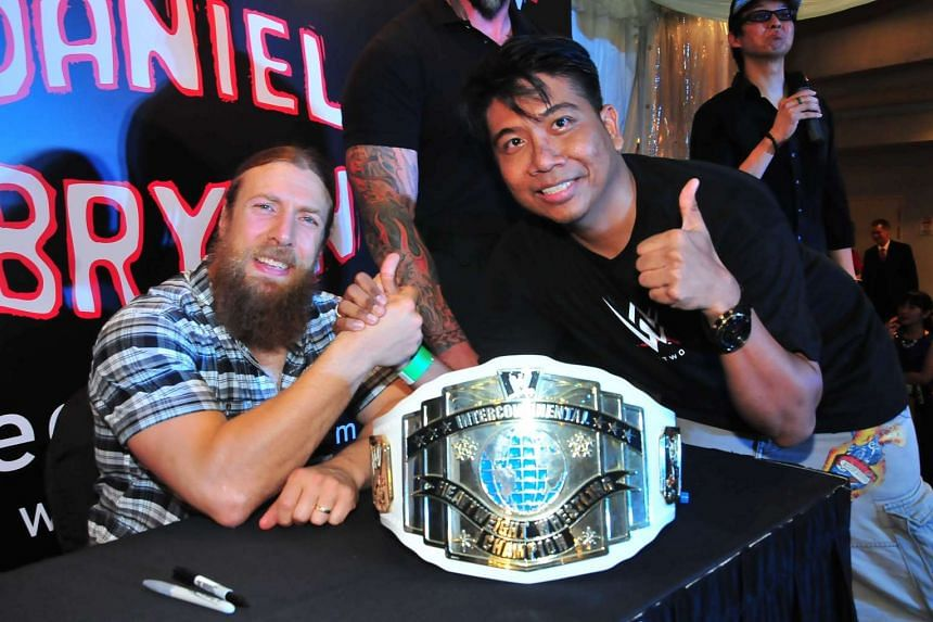WWE fan Shaharuddie Abdullah poses with WWE superstar Daniel Bryan at a meet and greet at Bugis Junction on Dec 9, 2015.