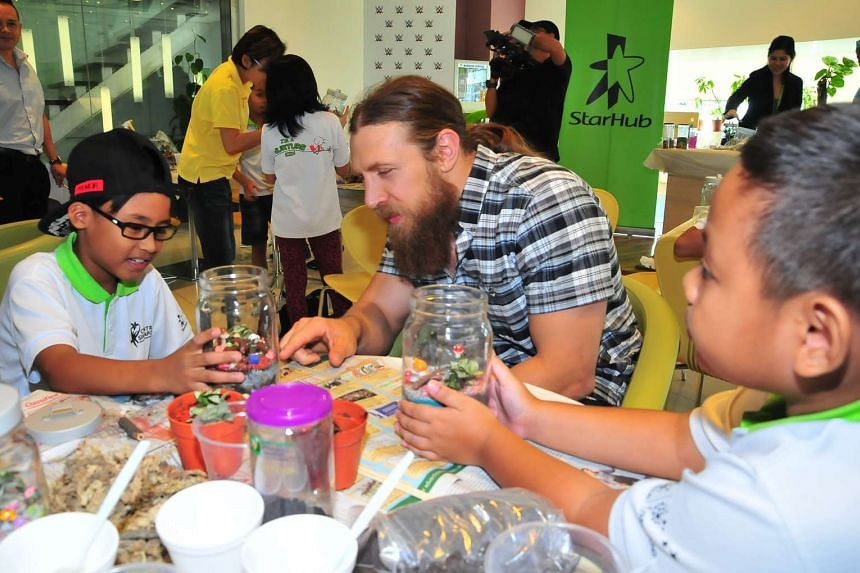 WWE's Daniel Bryan helping children from Central Singapore CDC's Nurture 2.0 programme create their own terrariums on Dec 9, 2015.