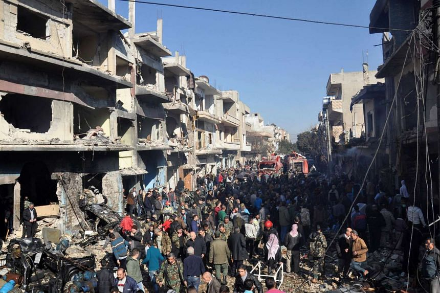 Syrians gather at the site of the blast in the Al-Zahraa neighbourhood in Homs.