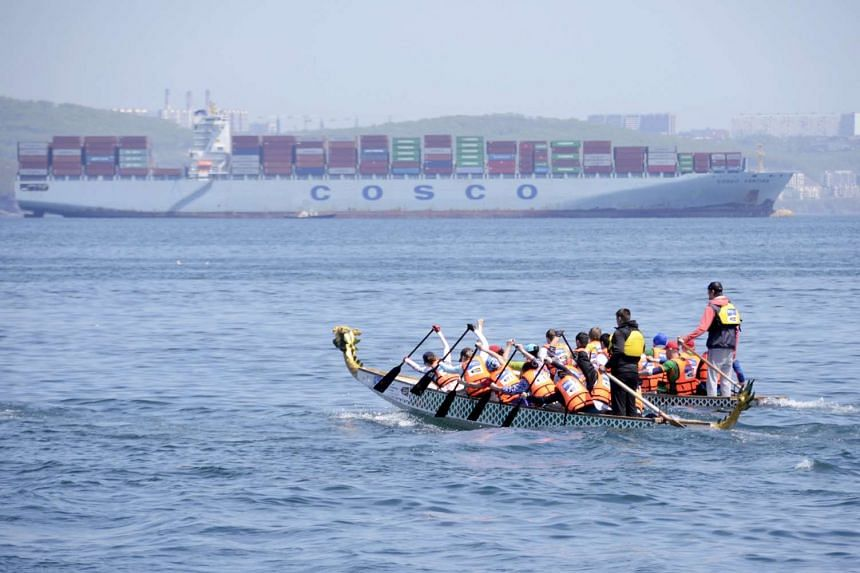 Dragon boaters against the backdrop of a Cosco container ship. Cosco and China Shipping Group are merging, in a move showing China's intent to create huge companies whose economies of scale would let them compete aggressively for overseas deals.