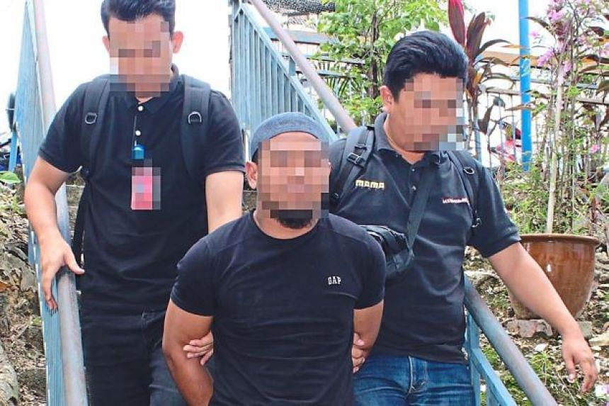 The suspect being escorted by members of Malaysia's special branch counter-terrorism division.