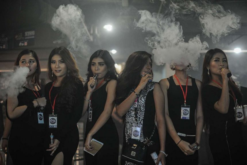 Promoters smoke electronic cigarettes during the VapeFair in Kuala Lumpur on Dec 5, 2015