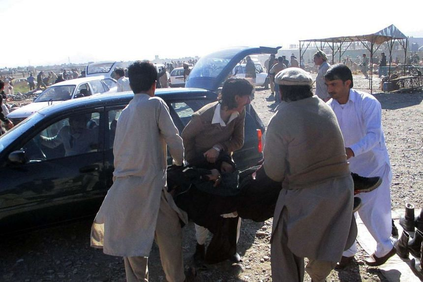 Pakistani men carry an injured blast victim after a bomb explosion at a market in Parachinar on Dec 13, 2015.