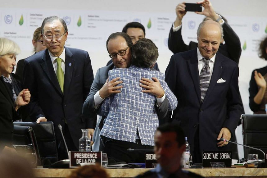 Ms Christiana Figueres, executive secretary of the United Nations climate convention, and French President Francois Hollande hug after the adoption of a historic global warming pact at the COP21 Climate Conference in Le Bourget on Dec 12, 2015.