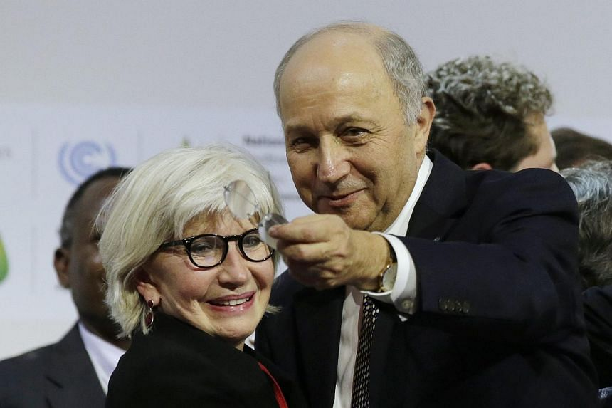 French Foreign Affairs Minister Laurent Fabius (right) and Laurence Tubiana, French head negotiator, react during the final plenary session at the World Climate Change Conference 2015.