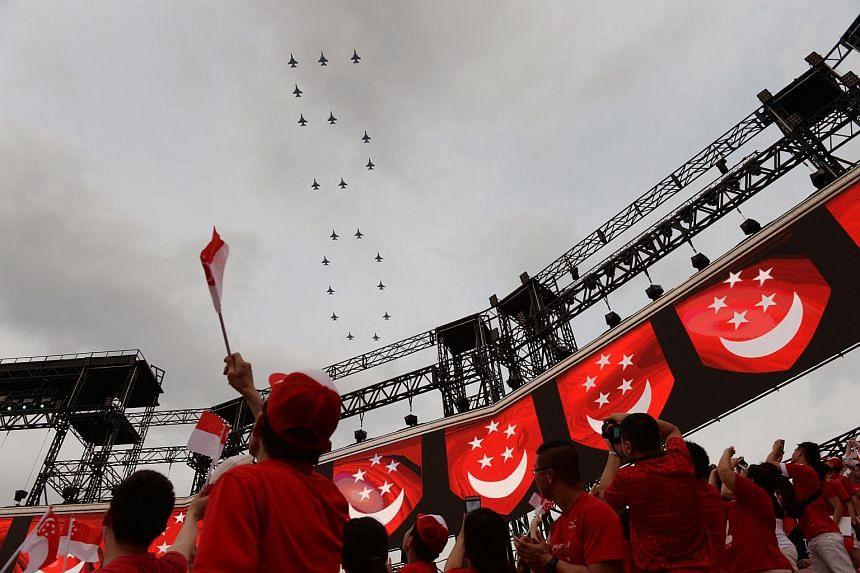 Spectators at the Golden Jubilee National Day Parade (NDP) watch F-16 fighter jets form the number 50 as part of the Republic of Singapore Air Force's salute.