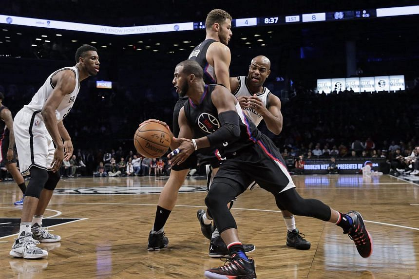 Los Angeles Clippers guard Chris Paul(center) dribbles around a screen set by teammate Blake Griffin (center behind) against the Brooklyn Nets during the first half of their NBA game at the Barclays Center in Brooklyn, New York, USA, Dec 12, 2015.