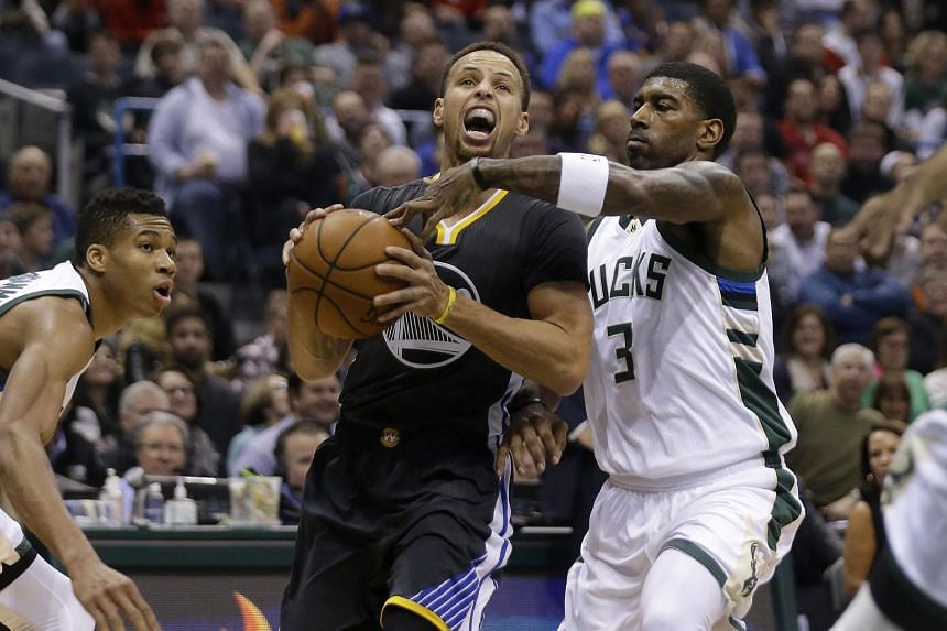 Stephen Curry #30 of the Golden State Warriors drives to the hoop during the first quarter against the Milwaukee Bucks.