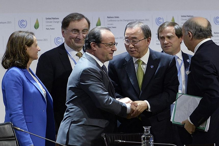 French President Francois Hollande shaking hands with UN Secretary-General Ban Ki Moon at the Paris climate summit yesterday. On the right, holding files, is French Foreign Minister Laurent Fabius.