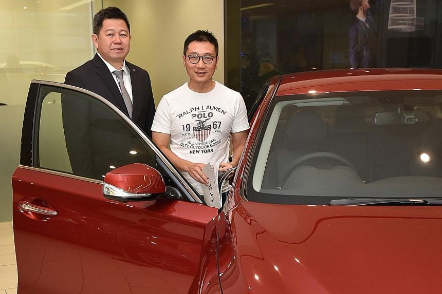 Mr Tan Chang Hong (in white T-shirt) did not let the heavy rain deter him from going to the Infiniti showroom in Leng Kee Road for a test drive of the Infiniti Q50 car yesterday. By doing so, Mr Tan, 47, seen here with Mr Michael Tan, 48, a brand con