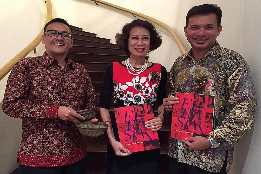 Artefact donors (from left) John Conceicao, Gerardine Donough-Tan and Kevin Aeria with copies of the book, The Eurasian Collection, which was launched yesterday. Mr Conceicao is holding brass cake moulds used to bake breudher, a type of cake introduc
