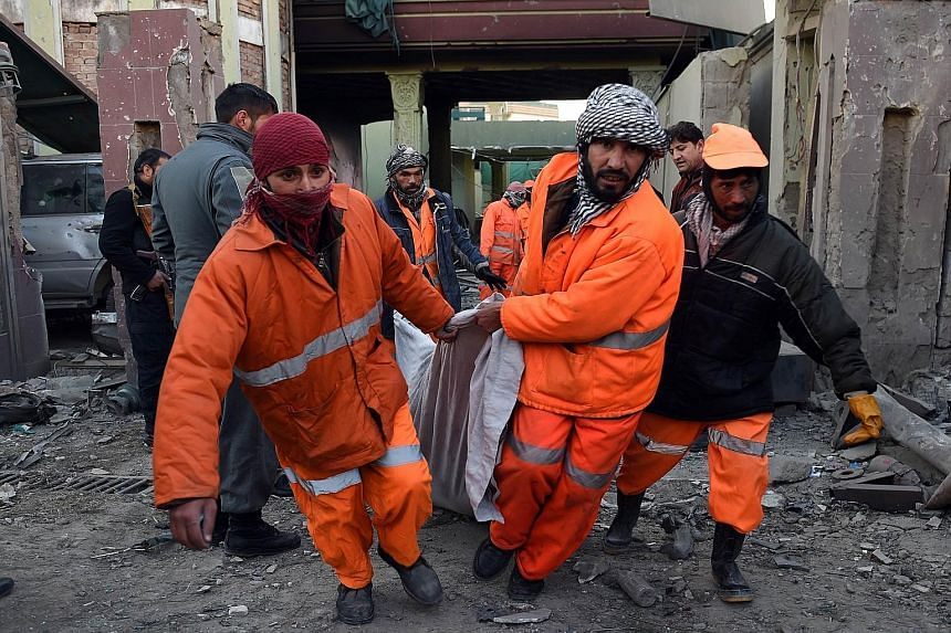 Afghan municipality workers carrying the body of a militant in front of buildings damaged by a car bomb attack in Kabul on Friday. Afghan officials said four assailants were killed during the attack.