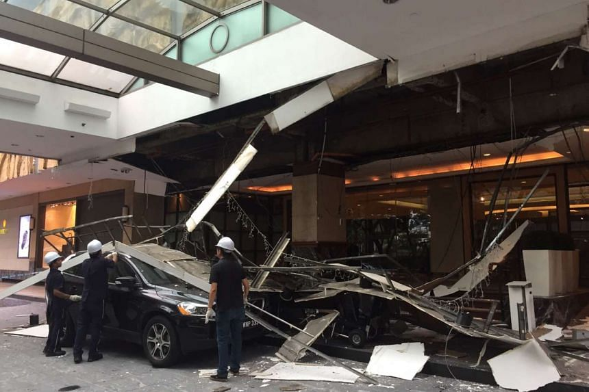 Workers clear the debris from the collapsed ceiling at the driveway of Hilton Singapore.
