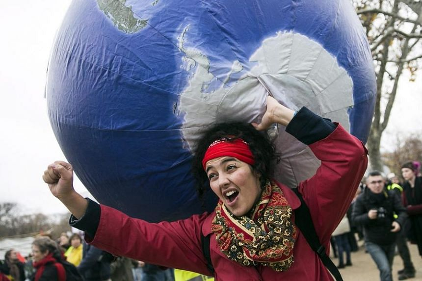 A woman carries an inflatable earth as thousands of people demonstrate in front of the Eiffel Tower for climate change in Paris on Dec 12, 2015.