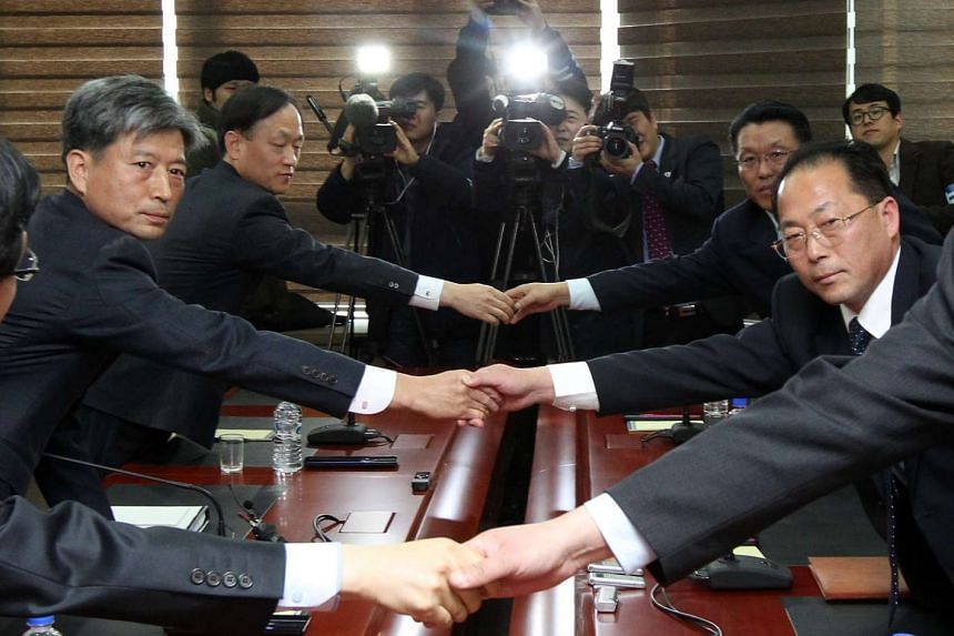 South and North Korean representatives shake hands at the start of the meet on Dec 11, 2015.