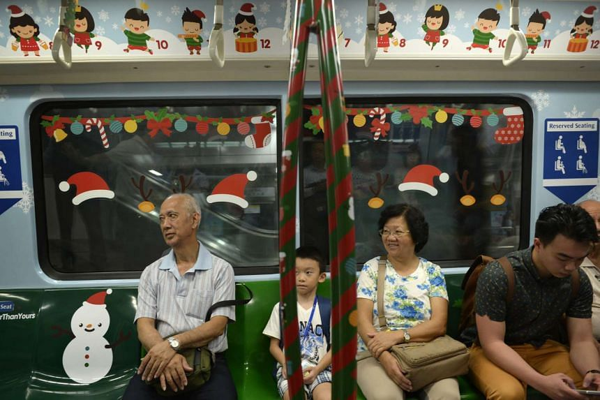 Passengers sit in a Christmas-themed train along the North South MRT Line on Dec 14, 2015.