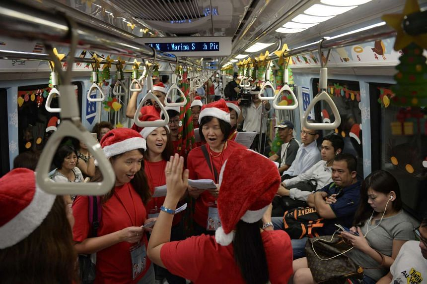 LTA staff sing Christmas carols on board a Christmas-themed train along the North South MRT Line on Dec 14, 2015.