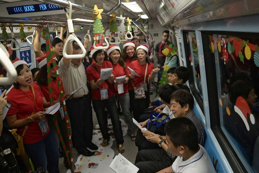 LTA staff sing Christmas carols with Transport Minister Khaw Boon Wan  (seated) and students of Pathlight School on board a Christmas-themed train along the North South MRT Line on Dec 14, 2015.