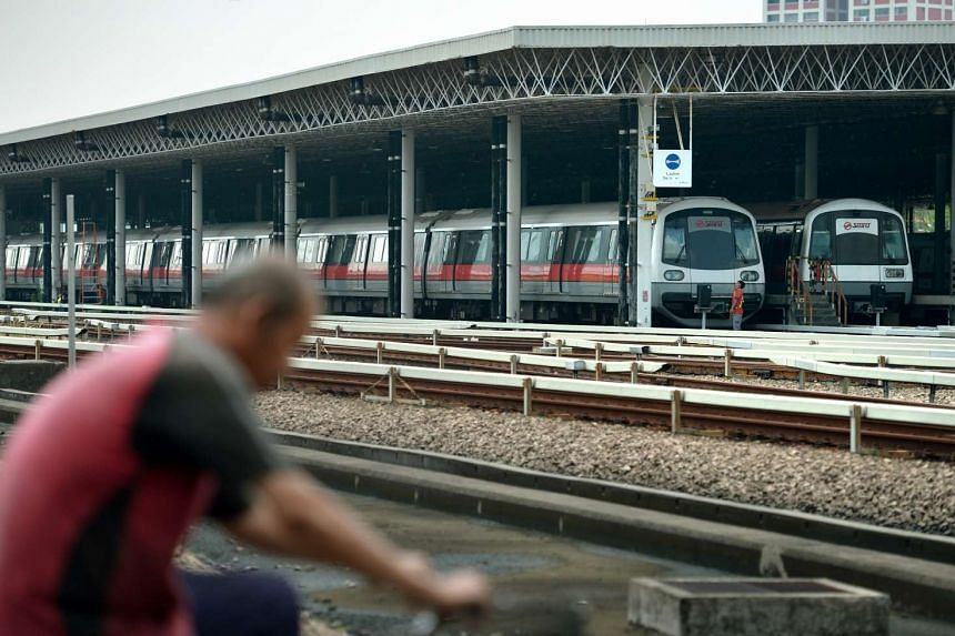SMRT staff cycles past SMRT trains parked at the Bishan depot on Nov 12, 2015.