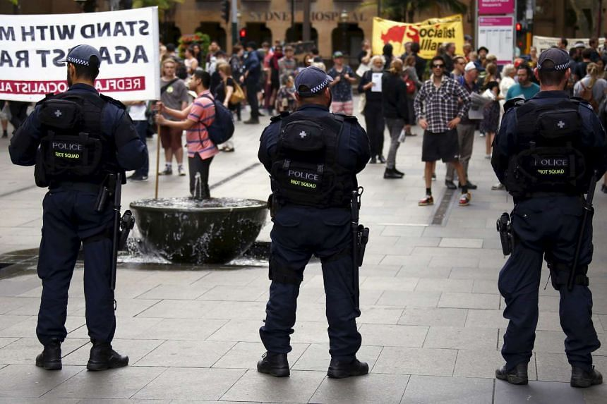 Police stand in front of anti-racism supporters during a rally in central Sydney, Australia, Nov 22, 2015.