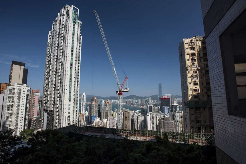 A crane operates next to residential buildings in the Mid-Levels area of Hong Kong.