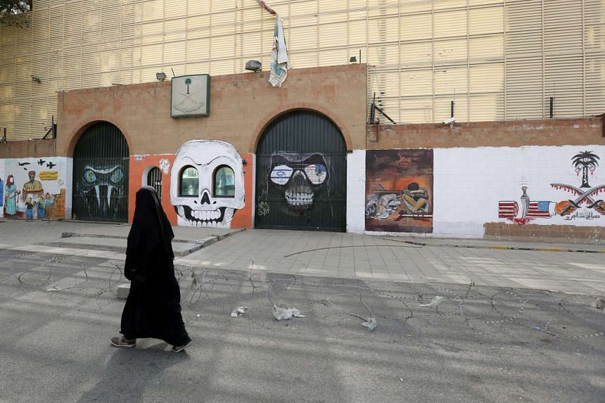 A Yemeni woman walks past graffiti sprayed on the wall of the Saudi embassy in Yemen.