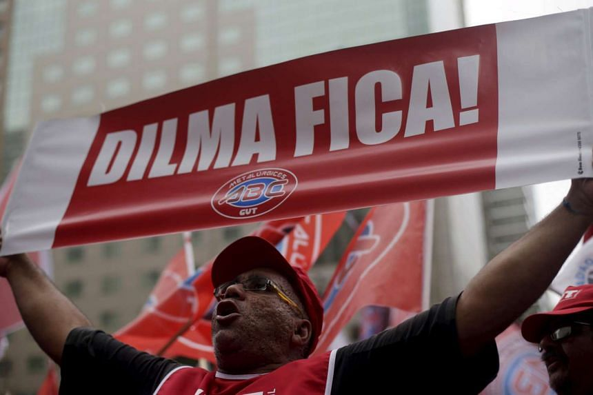 """A demonstrator attends a protest against the impeachment proceedings against Brazil's President Dilma Rouseff, in Rio de Janeiro, Brazil on Dec 8, 2015. The banner reads, """"Dilma stay!"""""""