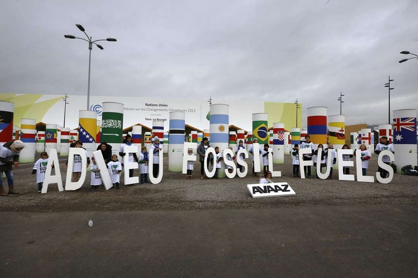 Children display giant letters reading 'Adieu (Bye) Fossil Fuels' in Le Bourget, north of Paris, France, Dec 11, 2015.
