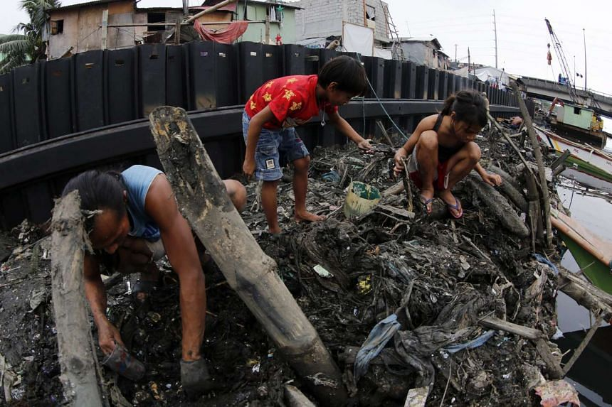 Filipinos collect useful materials next to a dike at an on-going flood control project in Paranaque city, south of Manila, Philippines on Dec 12, 2015.