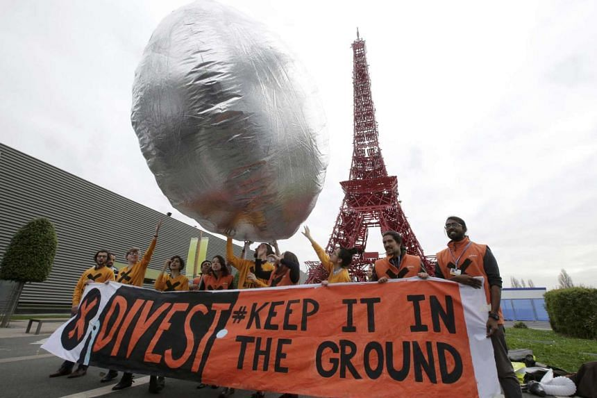 """Protestors with the message """"Divest. Keep it in the Ground"""" asking investment funds to move their money out of fossil fuels at the COP21 in Le Bourget, near Paris, France, Dec 2, 2015."""