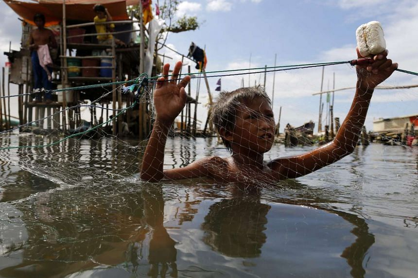 A Filipino boy holds a fishing net at a coastal village in Malabon city, east of Manila, Philippines on Dec 13, 2015.