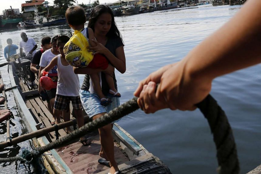 Filipino villagers disembark from a boat at a river in Malabon city, east of Manila.
