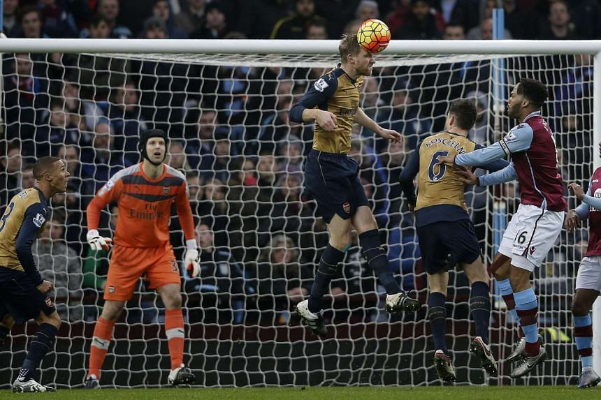 Arsenal's Czech goalkeeper Petr Cech (2L) watches as Arsenal's German defender Per Mertesacker jumps to clear the ball during the English Premier League football match between Aston Villa and Arsenal at Villa Park in Birmingham, central England on De