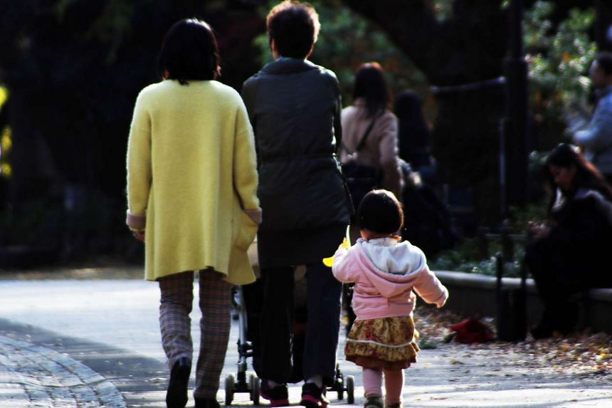 A family strolling at a park in Tokyo.