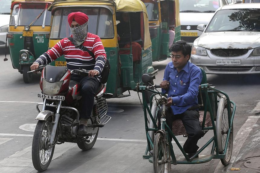 An Indian Sikh man uses handkerchief as protective mask against the smog as he rides a motorcycle in a busy street of New Delhi, India, Dec 8, 2015.