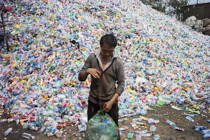 This photo taken on Sep 17, 2015, shows a Chinese labourer sorting out plastic bottles for recycling in Dong Xiao Kou village, on the outskirt of Beijing.