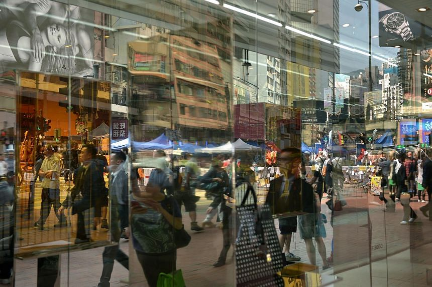A reflection of pedestrians crossing a traffic junction at Causeway Bay in Hong Kong.