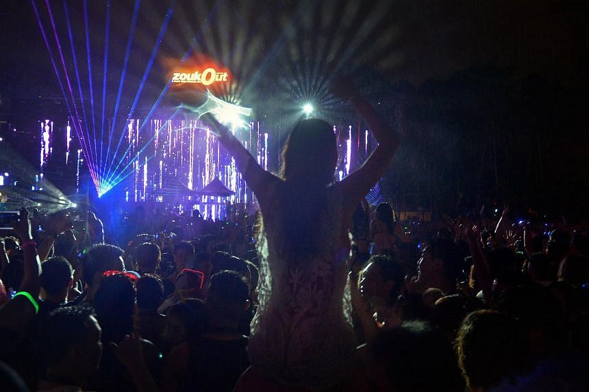 The crowd under the rain dancing to Rehab spinning on day two of Zoukout at the Siloso Beach in Sentosa.