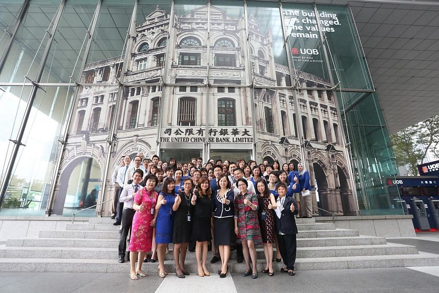 """UOB staff in front of the bank's main branch at Raffles Place. As part of its 80th anniversary celebrations, UOB has """"dressed up"""" its main branch by giving it the facade of its original headquarters, the Bonham Building."""