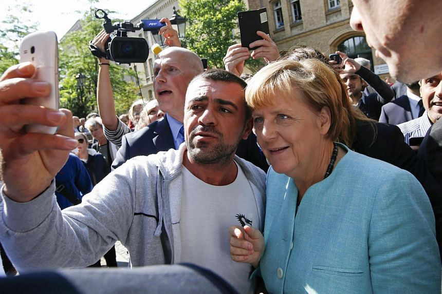 A migrant taking a selfie with German Chancellor Angela Merkel outside a refugee camp near the Federal Office for Migration and Refugees in Berlin.