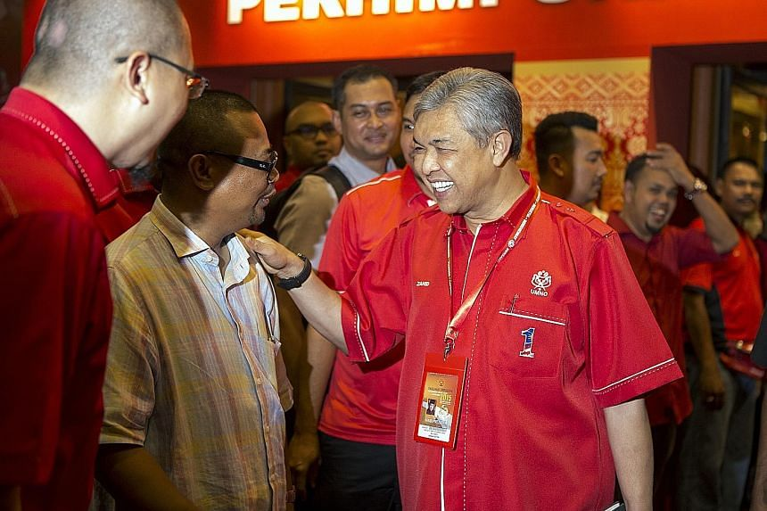Malaysia's Deputy Prime Minister Ahmad Zahid Hamidi (right) greeting supporters as he arrived for the Umno General Assembly at the Putra World Trade Centre in Kuala Lumpur on Tuesday. Prime Minister Najib Razak was in the spotlight but the man by his