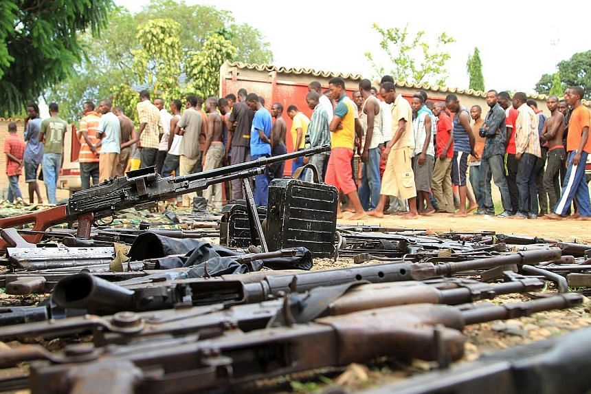 Suspected fighters being paraded before the media by Burundian police near a recovered cache of weapons after clashes in the capital Bujumbura last Saturday.