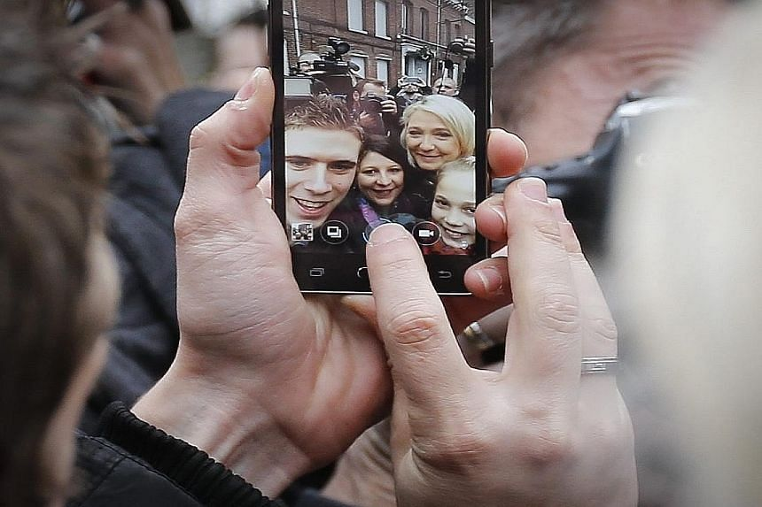 National Front leader Marine Le Pen (on the right in cellphone screen) posing for a wefie with supporters after casting her vote at a polling station in Henin- Beaumont yesterday.
