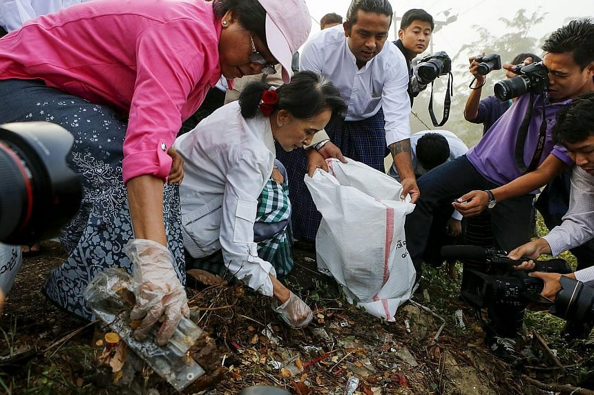 Myanmar's pro-democracy leader, Ms Aung San Suu Kyi, helping to collect rubbish in Kawhmu township, on the outskirts of Yangon, yesterday.