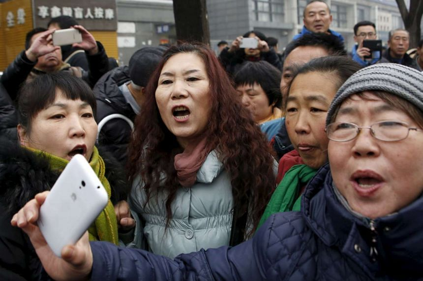 Supporters of China's rights lawyer Pu Zhiqiang shout slogans near a court  in Beijing where Pu's trial is being held.